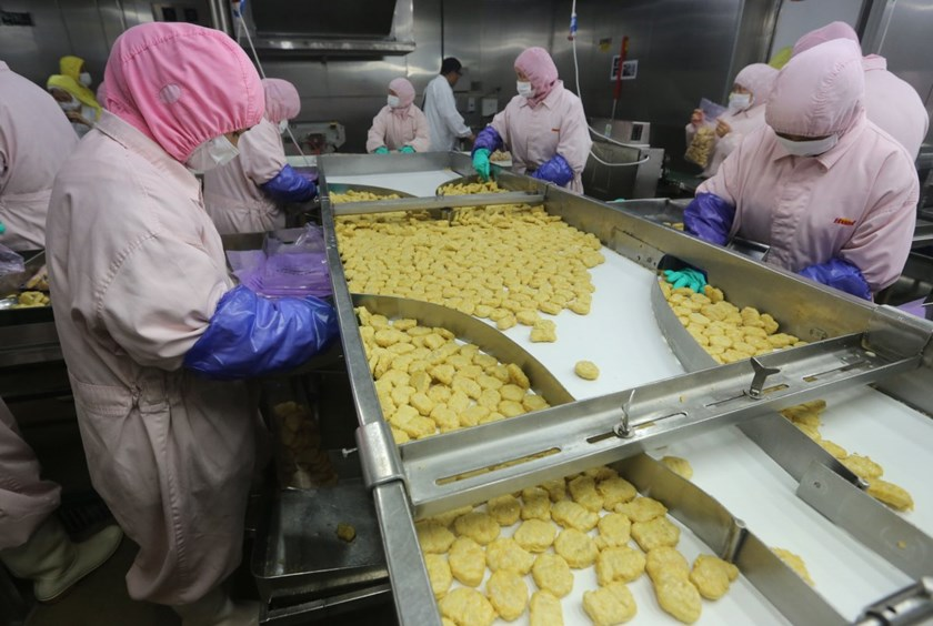 Employees stand during a seizure conducted by officers from the Shanghai Food and Drug Administration, at the Husi Food factory in Shanghai, July 20, 2014. Employees work at a production line prior to a seizure conducted by officers from the Shanghai Food