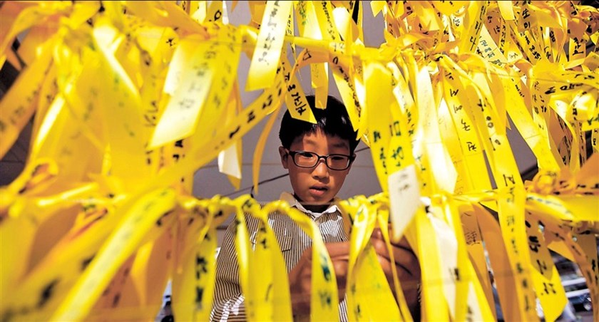 A boy ties a yellow ribbon dedicated to the missing and dead passengers of the sunken passenger ship Sewol, on a wire at Seoul City Hall Plaza May 1, 2014.