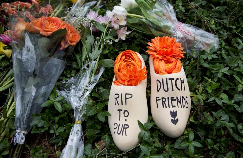 A message of sympathy for the victims of the flight MH17 disaster, is written on a wooden klomp, a traditional Dutch footwear for farmers, placed together with bouquet of flowers in front of the Netherlands Embassy in Washington, Monday, July 21, 2014.