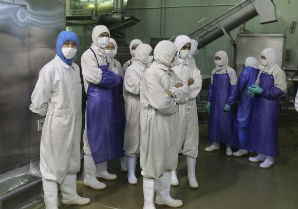 Employees stand during a seizure conducted by officers from the Shanghai Food and Drug Administration, at the Husi Food factory in Shanghai, July 20, 2014.