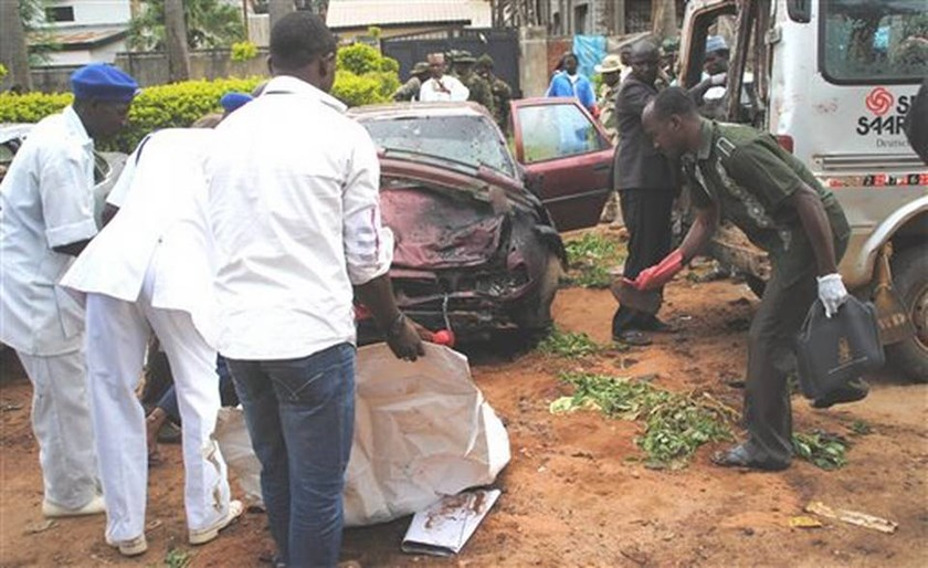 Workers pick items at the scene of a bombing in Kaduna July 23, 2014.