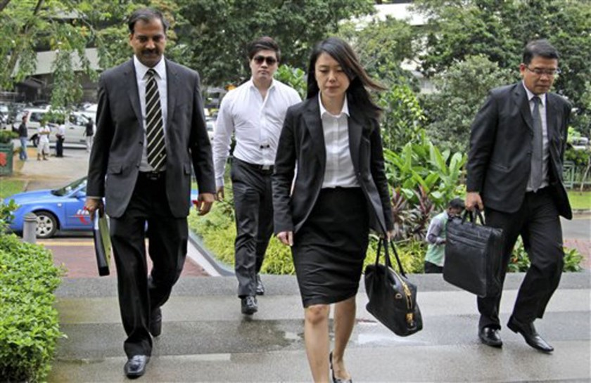 Eric Ding, second left, arrives at the subordinate courts with his lawyers on Monday, July 15, 2013 in Singapore.