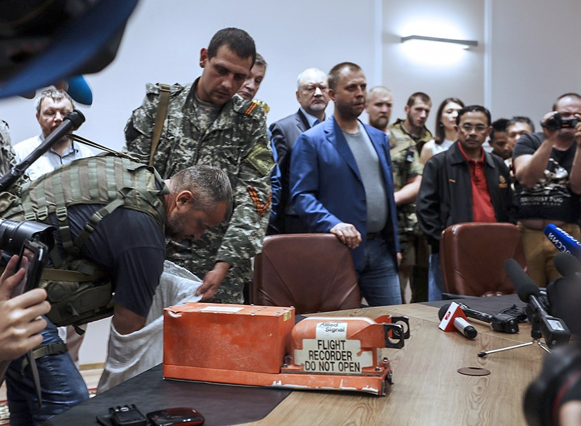 A pro-Russia separatist hands over the black box belonging to Malaysia Airlines flight MH17 to Malaysian representatives in Donetsk on July 22, 2014.