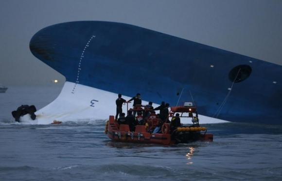 Maritime police search for missing passengers in front of the South Korean ferry ''Sewol'' which sank at the sea off Jindo April 16, 2014.