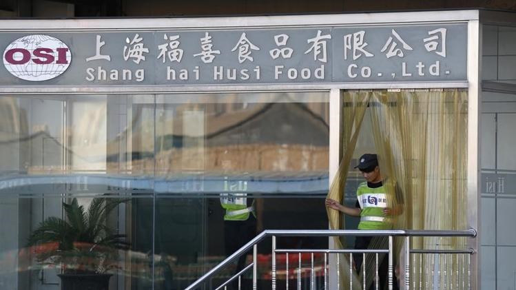 Security guards stand inside the Husi Food factory in Shanghai July 23, 2014.