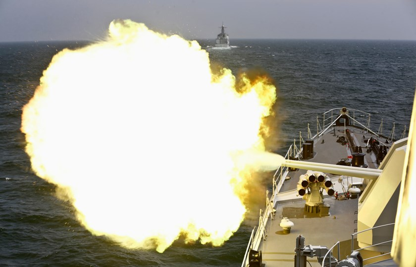 A Chinese navy vessel fires its cannon during a naval drill outside Shanghai in the East China Sea on May 24, 2014