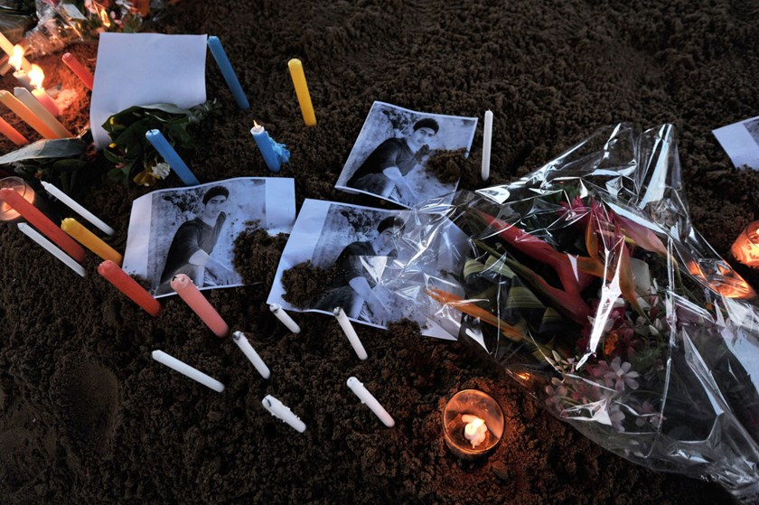 Flowers and candles are placed next to pictures of one of the Lebanese victims of the Air Algerie crash at Ouagadougou Airport, on July 26, 2014.
