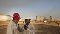 Workers for China Petroleum Engineering & Construction Corp. (CPECC) talk on a mobile handset by oil storage tanks near Melut, in the Upper Nile, Sudan.