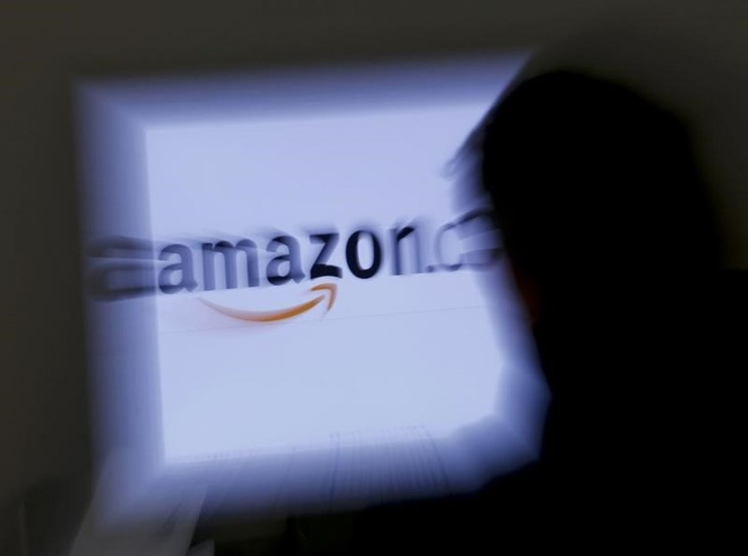 A zoomed illustration image of a man looking at a computer monitor showing the logo of Amazon is seen in Vienna. Photo: Reuters