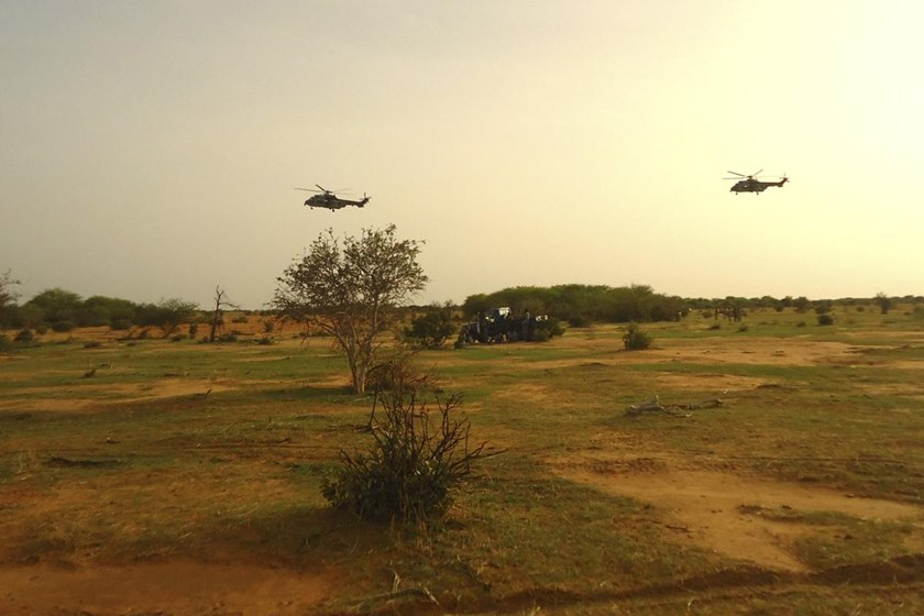 French military helicopters fly above the crash site of Air Algerie flight AH5017 near the northern Mali town of Gossi