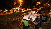 Residents carry a wounded person following a blast in Kaohsiung in southern Taiwan early on August 1, 2014.