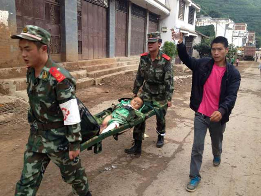 Rescuers carry an injuried child on a stretcher after a 6.5 magnitude earthquake hit the Zhaotong city region in southwest China's Yunnan province, on August 3, 2014.