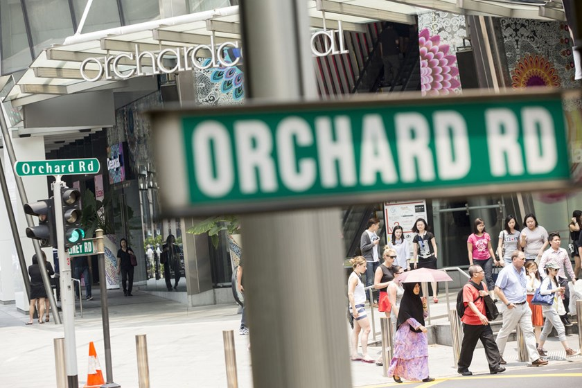 Pedestrians and shoppers cross Orchard Road shopping strip in Singapore.