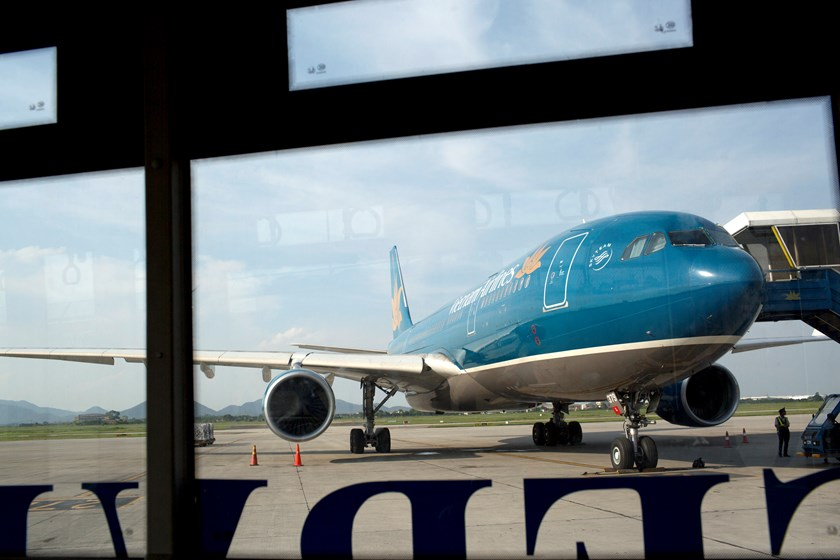 A Vietnam Airlines Corp. aircraft, photographed through the window of a shuttle bus, stands on the tarmac at Noi Bai International Airport in Hanoi. Photo credit: Bloomberg