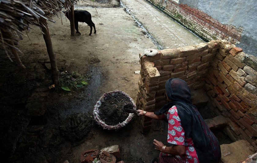 A woman collects human waste while cleaning a toilet in Nekpur village, Uttar Pradesh, India.