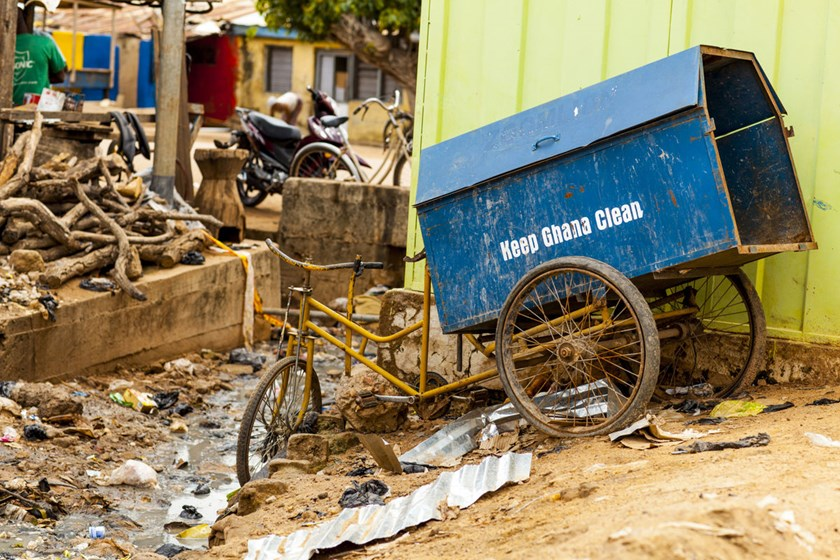 "A garbage collection bicycle sits with the slogan ""Keep Ghana clean"" by an open sewer river. The World Bank will give Ghana $150 million in grants to improve access to potable water and basic toilets for the poorest residents of Accra, where most roads ar"