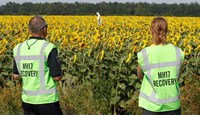 Forensic experts look at a makeshift marker denoting evidence during recovery work at the site of the downed Malaysian airliner MH17 near the village of Rozsypne in the Donetsk region August 4, 2014.
