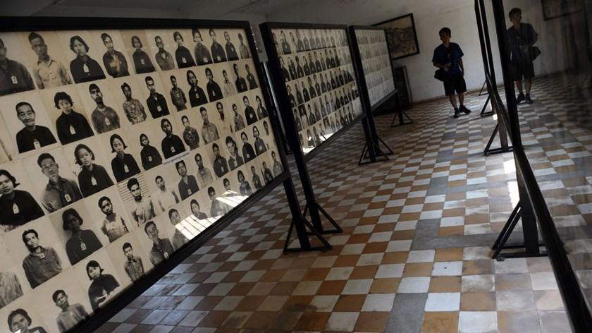 A person looks at photographs of prisoners on display at the Tuol Sleng genocide museum, a former prison used by the Khmer Rouge to imprison and torture Cambodians during the 1970s, in Phnom Penh.