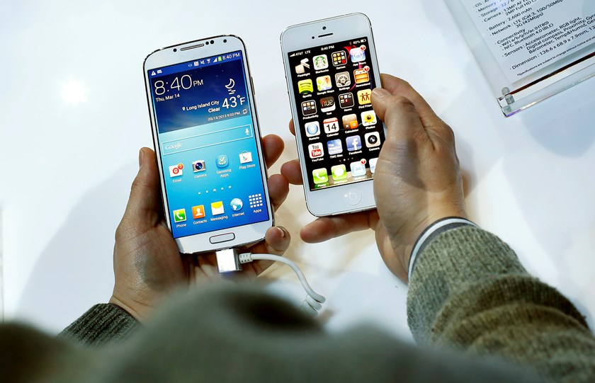 A Samsung Electronics Co. Galaxy S4 smartphone, left, and an Apple Inc. iPhone 5 in New York.