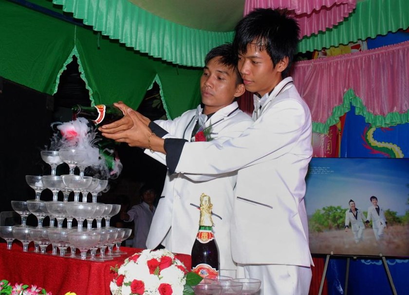 Nghi (L) and Luan pour champagne during their same-sex wedding party in the southern province of Binh Phuoc on April 27, 2014
