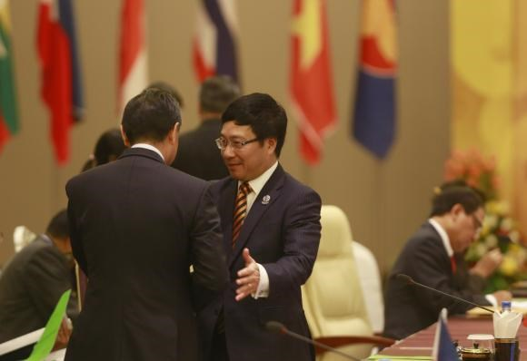 Chinese Foreign Minister Wang Yi and his Vietnamese counterpart Pham Binh Minh (R) shake hands during the ASEAN-CHINA Ministerial Meeting at the Myanmar International Convention Centre (MICC) in Naypyitaw, August 9, 2014.