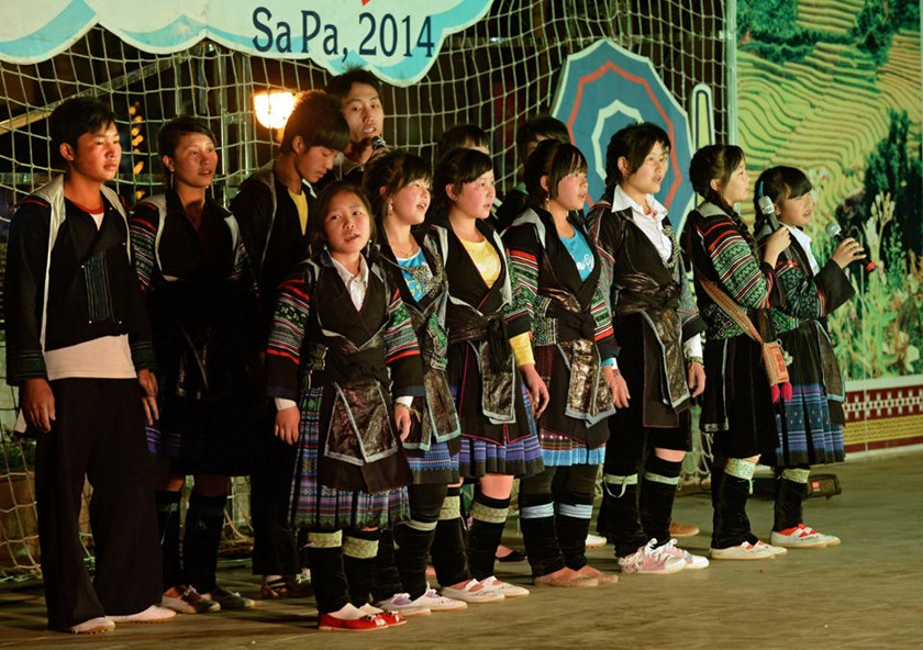 Hmong youth perform a song at a public evening show in the northwestern mountainous town of Sapa on May 11, 2014