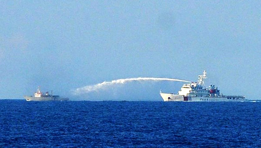 A Chinese ship (R) sprays water cannon at a Vietnamese coast guard boat operating near an oil rig China deployed illegally in waters claimed by Vietnam in May 2014.