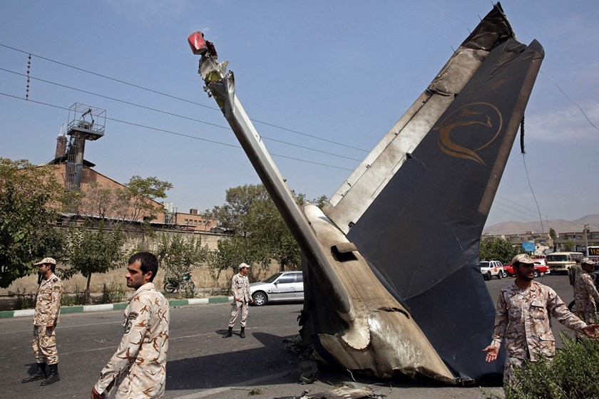 Iranian Revolutionary Guards stand alert at the site of the wreckage of a passenger plane crash near the capital Tehran, Iran, Sunday, Aug. 10, 2014. An Iranian passenger plane crashed Sunday while taking off from an airport near the capital, Tehran, kill