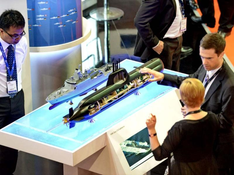 Visitors look at an exhibit of a naval vessel and a submarine displayed at the International Maritime Defence Exhibition (IMDEX) Asia 2013 in Singapore. Photo: AFP