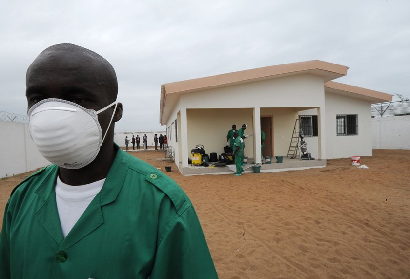 A man wearing a protective mask stands in front of an isolation center for people infected with the Ebola virus at the airport in Abidjan, Ivory Coast.