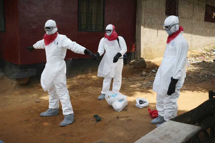 A Liberian health department burial team disinfects their protective clothing after retrieving the body of a woman suspected of dying of the Ebola virus on Aug. 14, 2014 in Monrovia.