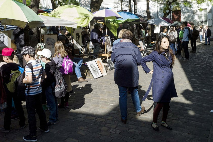 A Chinese tourist stands in a street of the Montmartre neighborhood in the city of Paris.
