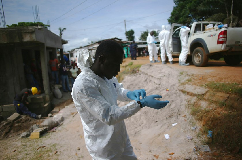 A burial team prepares to collect the dead body of a woman suspected of dying of the Ebola virus in Monrovia, Liberia, on Aug. 14, 2014.