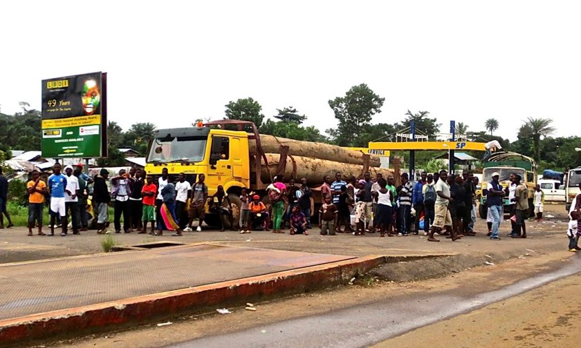 A crowd gathers near a checkpoint, which controls the movement of people in and out of Ebola-hit regions, at the entrance to Bomi county in northwestern Liberia August 11, 2014.
