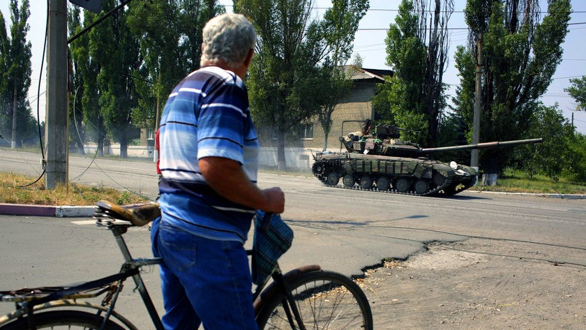 A resident watches a Ukrainian tank passing by in the small eastern city of Vuglegirsk, Ukraine, on Aug.
