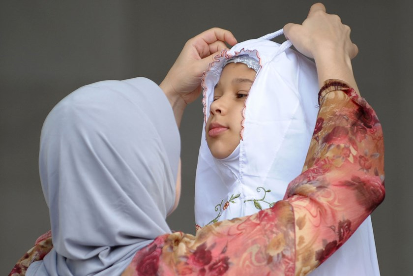 A mother adjusts her daughter's headscarf in Kuala Lumpur. Most women drop out of the workforce to look after their children due to a lack of childcare facilities.
