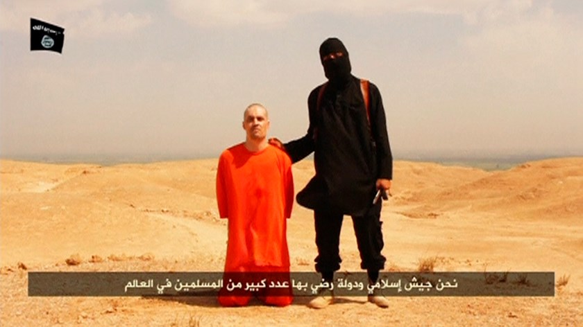A masked Islamic State militant holding a knife speaks next to man purported to be U.S. journalist James Foley at an unknown location in this still image from an undated video posted on a social media website.