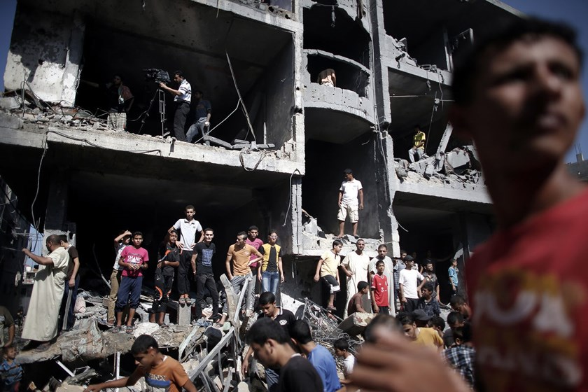 Palestinian gather around the rubble of a building destroyed following an Israeli military strike in Rafah in the south of the Gaza Strip on August 21, 2014