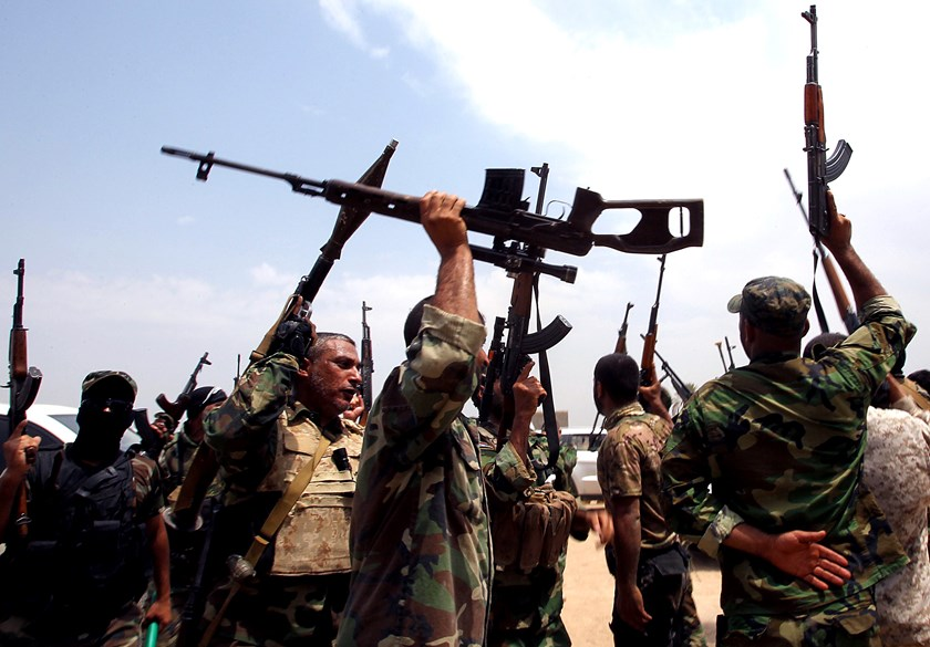 Shiite Muslim fighters from the Saraya al-Salam, a group formed by Iraqi Shiite Muslim cleric Moqtada al-Sadr and tasked with defending the holy sites of Shiite Islam, brandish their weapons as they hold a position on the Jurf al-Sakhr front line, the sce