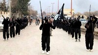 This undated file image posted on a militant website on Tuesday, Jan. 14, 2014, which has been verified and is consistent with other AP reporting, shows fighters from the al-Qaida linked Islamic State of Iraq and the Levant (ISIL) marching in Raqqa, Syria
