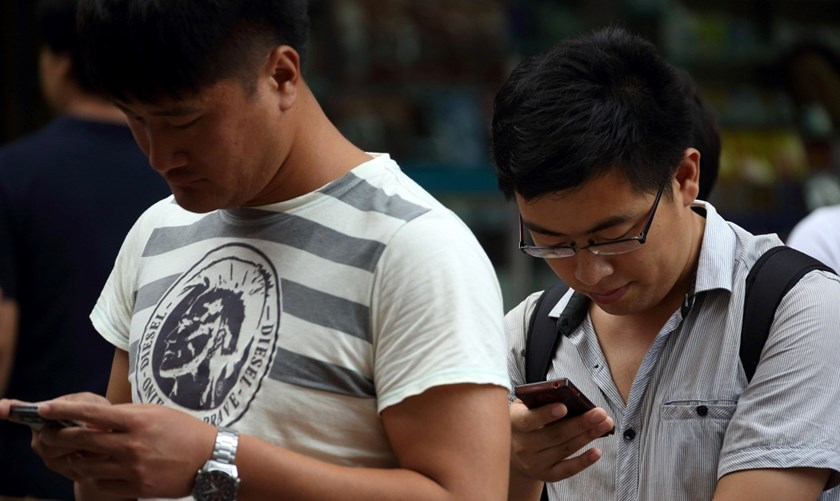 Pedestrians use mobile phones in Dalian, China, on Tuesday, Sept. 10, 2013. Apple Inc. is close to securing deals with China Mobile and Japan's NTT DoCoMo Inc. to sell iPhones in Asia's biggest markets.