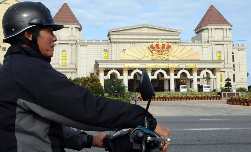 "A motorbike taxi driver waits for a customer in front of the Crown Casino in Danang, Vietnam. Under the draft proposal, Vietnamese who are at least 21 and have ""sufficient financial ability"" will need to pay an entrance fee to gamble in casinos, according"