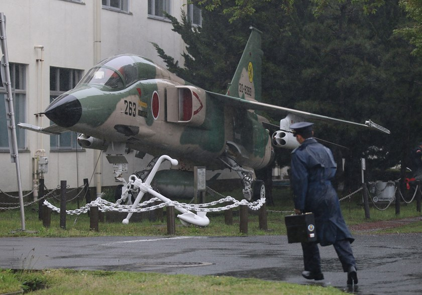 A National Defense Academy of Japan (NDA) cadet runs past a military aircraft on display at the NDA campus in Yokosuka, Kanagawa Prefecture, Japan.