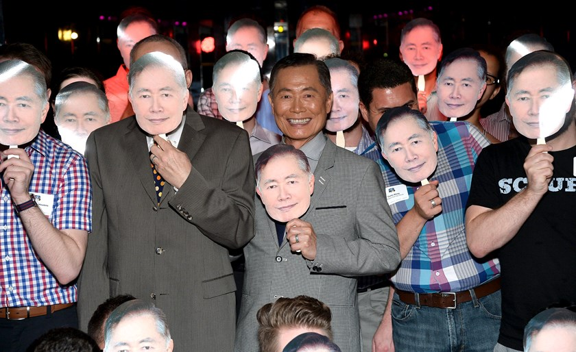 "George Takei, center, and his spouse Brad Takei, left, with attendees during DirecTV's ""To be Takei"" media reception at The General NYC on July 2, 2014 in New York City."