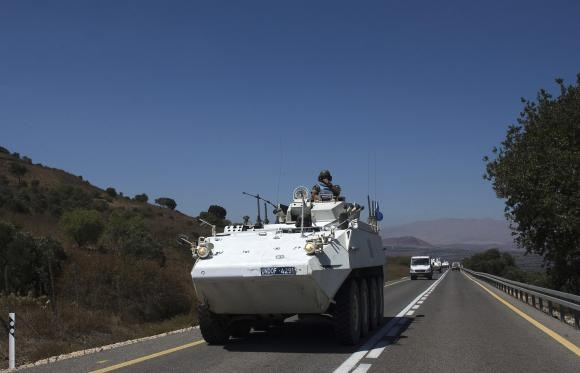 A member of the U.N. Disengagement Observer Force (UNDOF) rides atop an armoured vehicle near the Quneitra border crossing on the Israeli-occupied Golan Heights August 28, 2014.