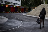 "A prostitute walks past so-called ""sex boxes,"" opened in 2013 with the aim of getting prostitution off Zurich's street. Like the finance industry, the sex industry has opted for a lower profile on the outskirts of town."