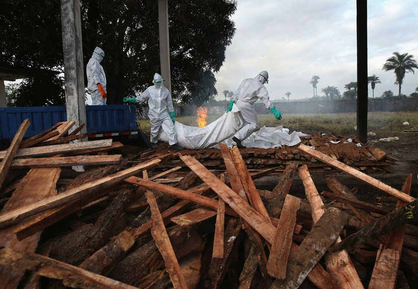 A burial team from the Liberian Ministry of Health piles the bodies of Ebola victims onto a funeral pyre at a crematorium in Marshall, Liberia.
