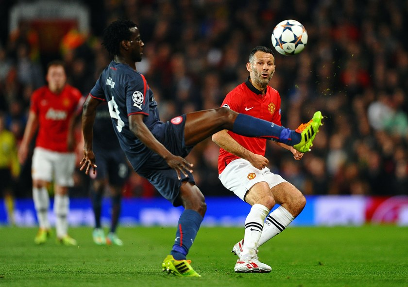 Ryan Giggs of Manchester United competes with Delvin N'Dinga of Olympiacos during the UEFA Champions League Round of 16 second round match between Manchester United and Olympiacos FC at Old Trafford on March 19, 2014.