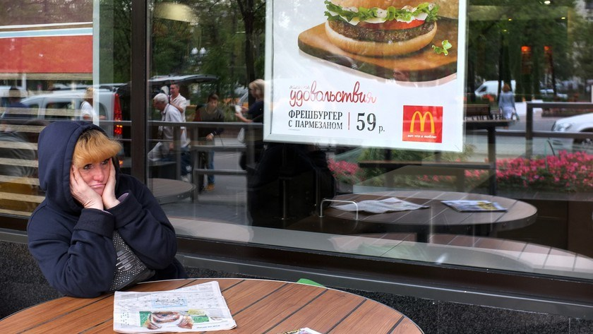 A woman sits at a table of a closed McDonald's restaurant, the first to be opened in the Soviet Union in 1990, in Moscow on Aug. 21, 2014.