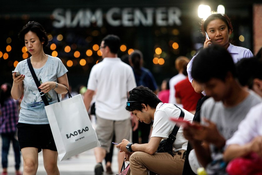 Shoppers sit in front of the Siam Center shopping mall in Bangkok, Thailand. The country's economy is showing signs of recovery after a military coup in May.